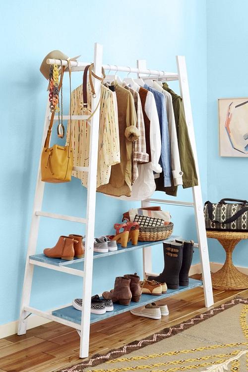 Arara de roupas e sapatos feita com duas escadas e duas tábuas.