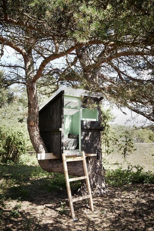 Casa na árvore com madeira pintada de verde e almofadas.
