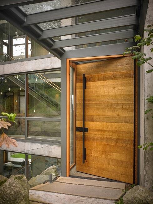 Porta de entrada feita de madeira contrastando com o concreto e aço ao redor.