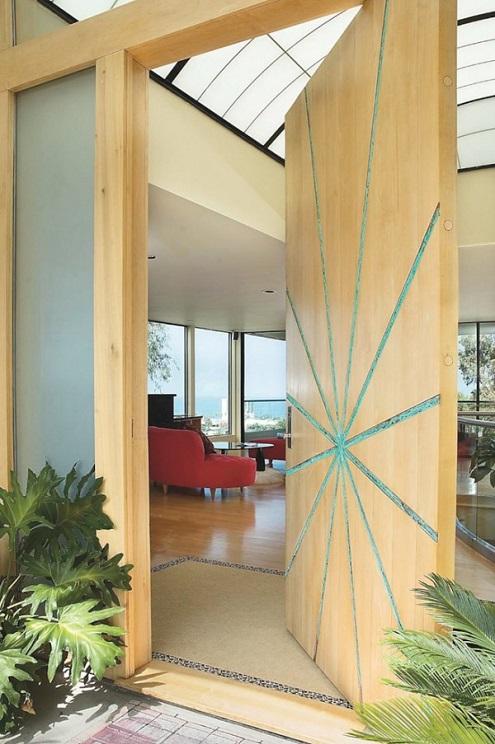 Porta de madeira clara com desneho de estrela em entrada de casa.