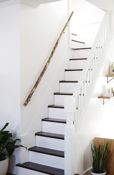 Corrimão de escada feito de madeira crua.