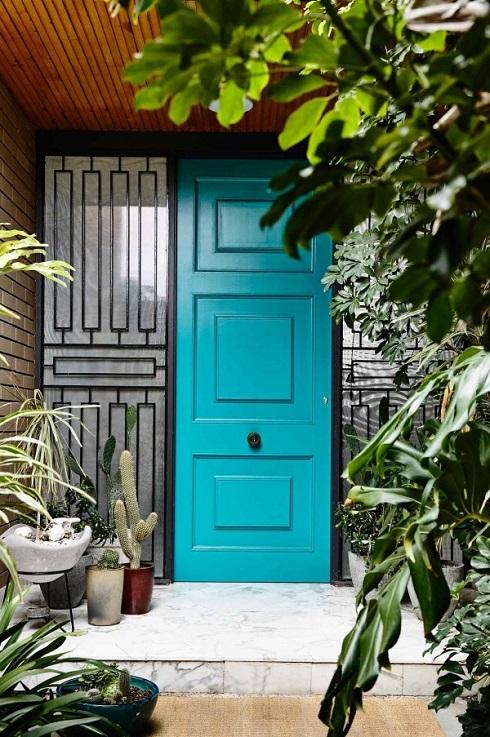 Porta de entrada pintada de azul em meio ao verde do jardim.