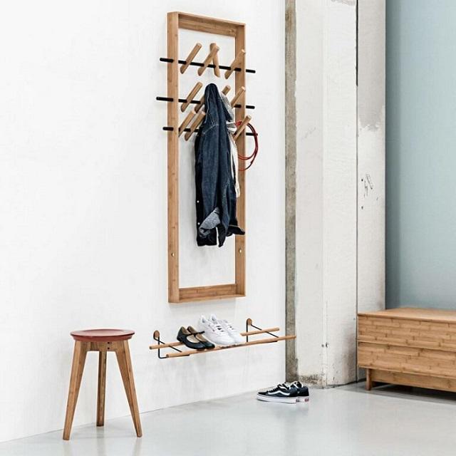 Cabideiro de madeira de parede com prateleira para sapatos e banquinho.