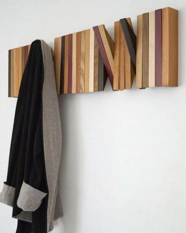 Cabideiro de parede feito de madeira que parece uma obra de arte.