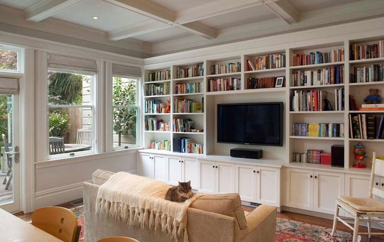 Estante branca feita de madeira em parede da sala de TV.