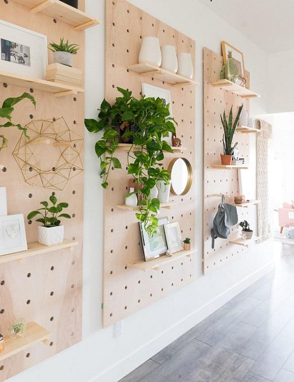 Painéis de madeira clara com prateleiras, no estilo estante, para plantas.