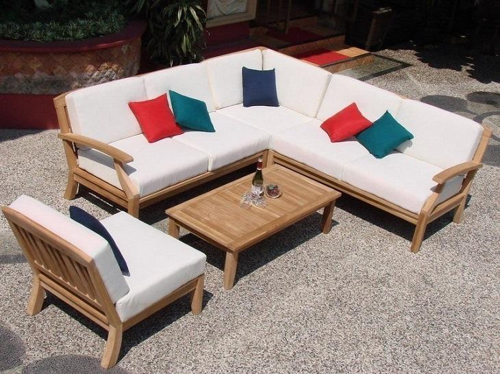 Sofá de madeira maciça clara em área externa.