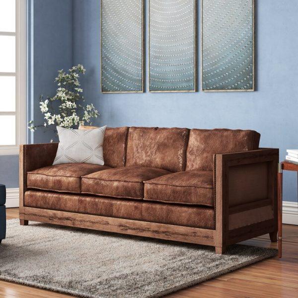 Sofá de madeira rústico com almofadas de couro com aparência envelhecida.
