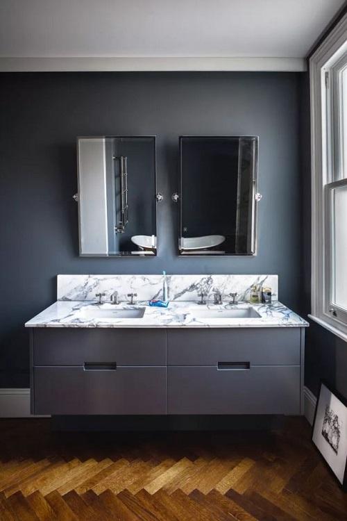 Banheiro cinza escuro com piso de parquete de madeira.