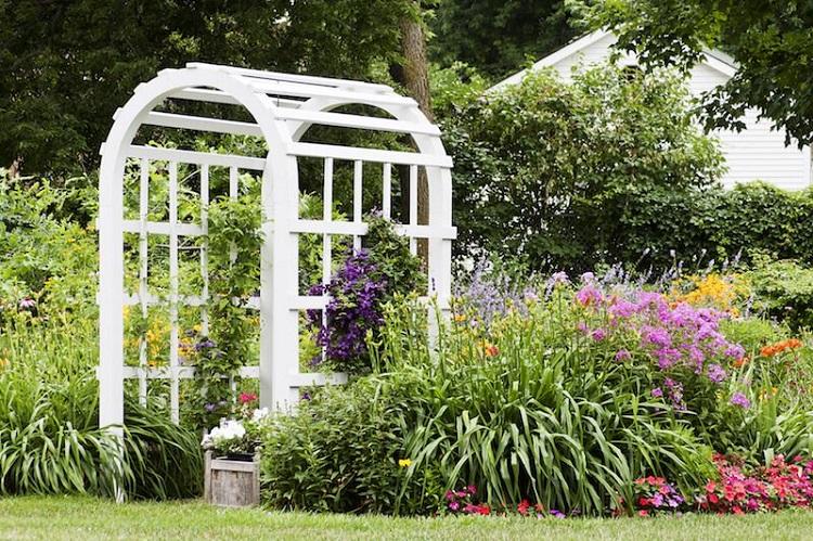 Caramanchão de madeira branca em estilo clássico num jardim.