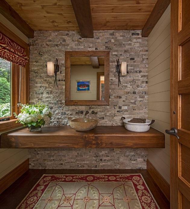 Banheiro combinando cores neutras: paredes bege, uma parede cinza de pedra e bancada, janela, porta e teto d emadeira com vigas expostas.