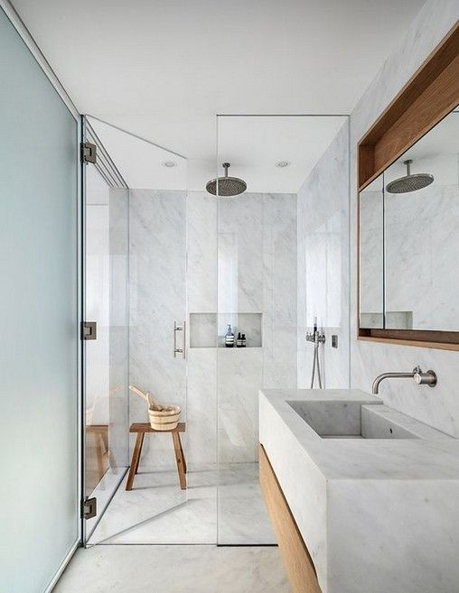 Banheiro cinza com toques de madeira clara e muita luz natural.