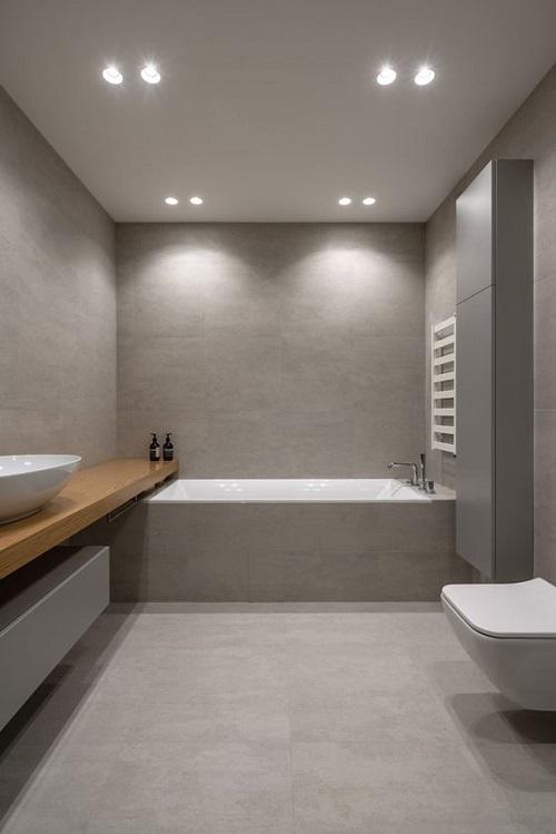 Banheiro cinza minimalista com bancada grande de madeira.