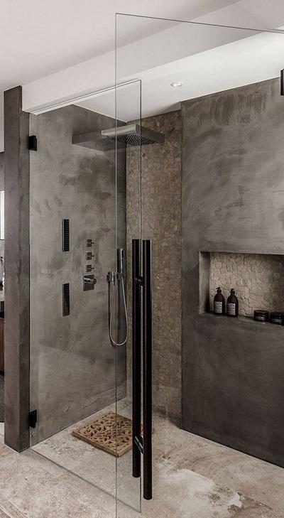 Banheiro cinza e madeira em tapete no box do chuveiro.
