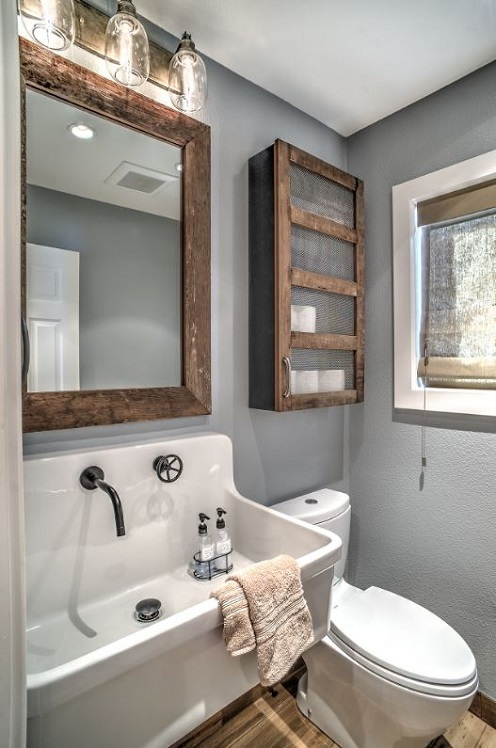Banheiro cinza com detalhes em madeira rústica.