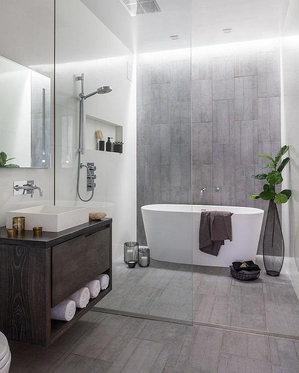 Banheiro com paredes brancas e uma parede cinza, piso cinza e balcão personalizado em madeira escura.