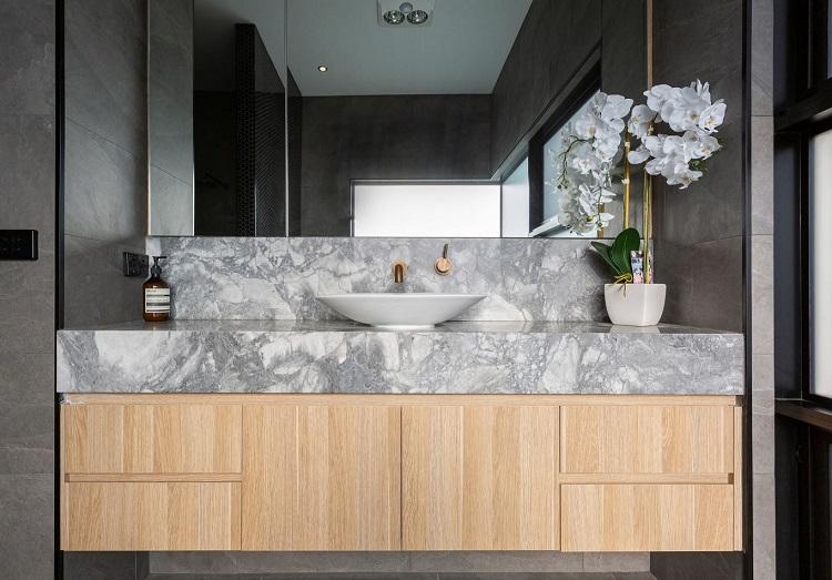 Banheiro cinza e madeira em estilo contemporâneo.