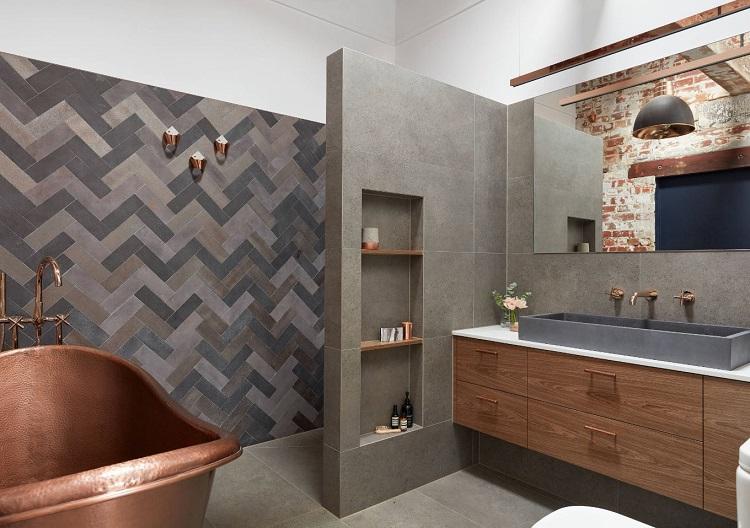 A cor cinza e detalhes em madeira combinam com espaço em estilo industrial como esse banheiro.