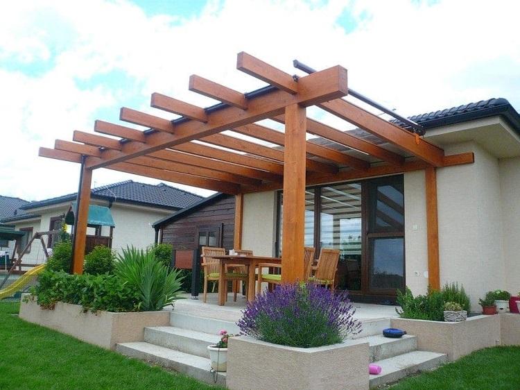 Pergolado de madeira integrado como varanda de casa branca.