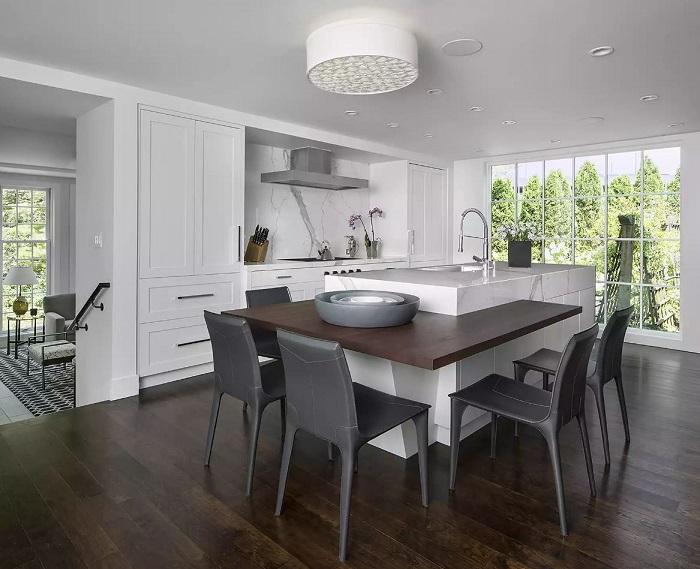 Cozinha minimalista com mesa de madeira embutida no centro do cômodo.