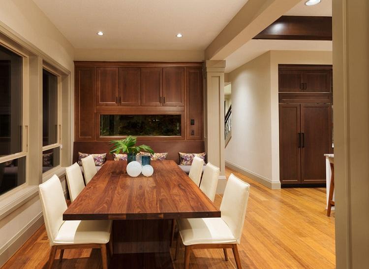 Mesa retangular em sala de jantar com cadeiras brancas.