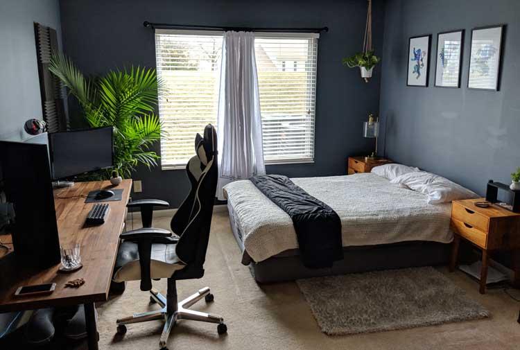 Escrivaninha de madeira para home office no quarto de paredes escuras.