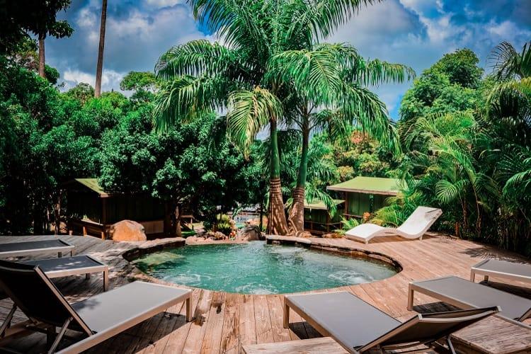 Piscina em deck de madeira suspenso em cenário tropical.