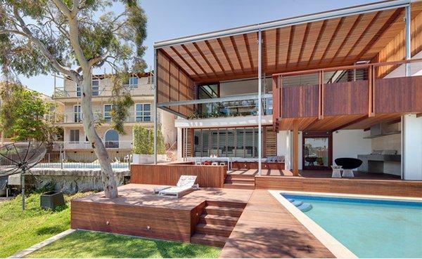 Casa com fachada de madeira e vidro com deck de piscina combinando.