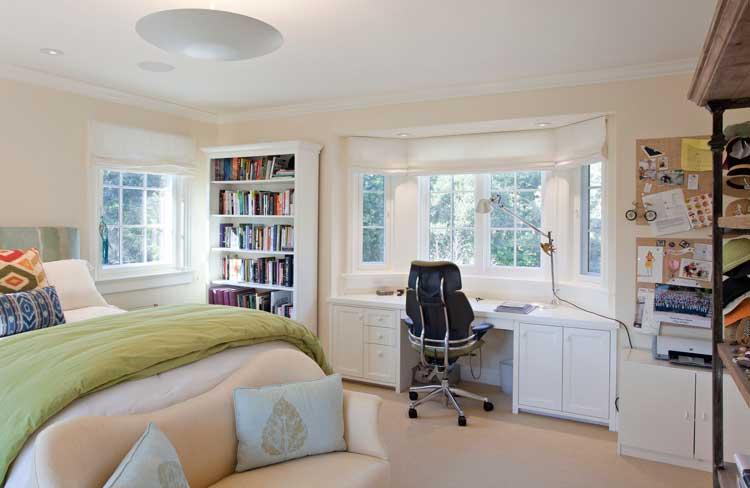 Quarto com escrivaninha instalado no espaço da janela.