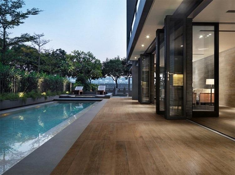 Deck de madeira sofisticado instalado em área com piscina retangular.