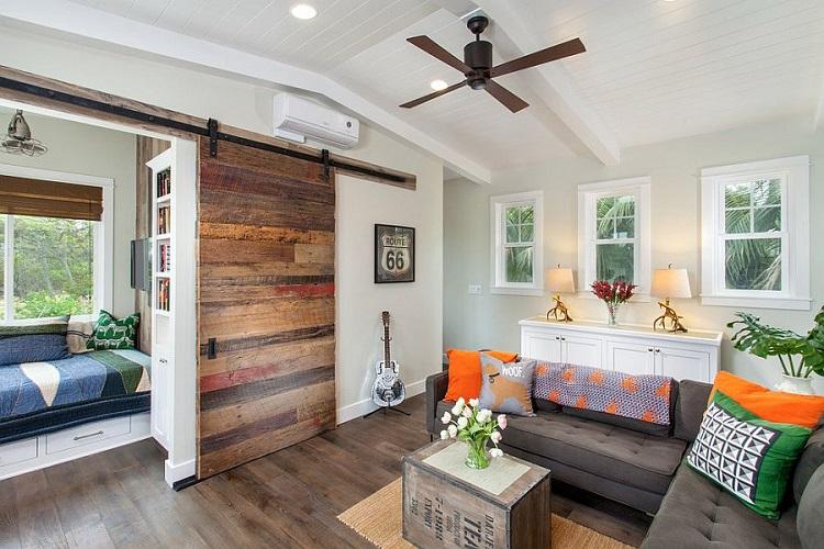 Porta de correr de madeira separando sala de estar de sala de leitura.