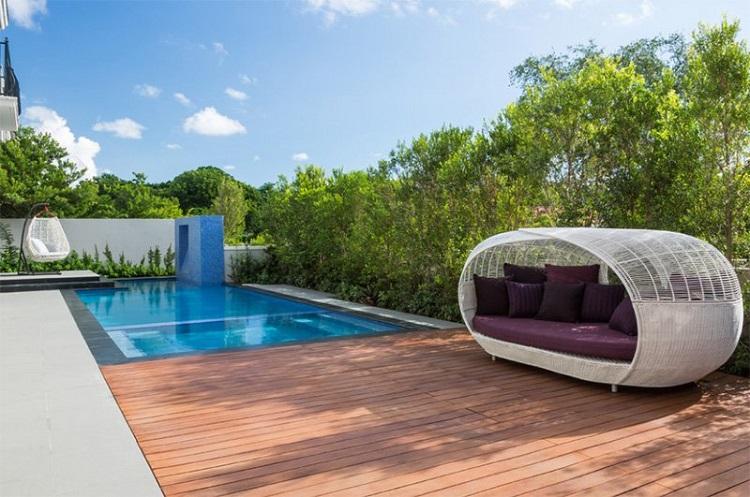 Área de piscina com móveis confortáveis instalados no deck de madeira.