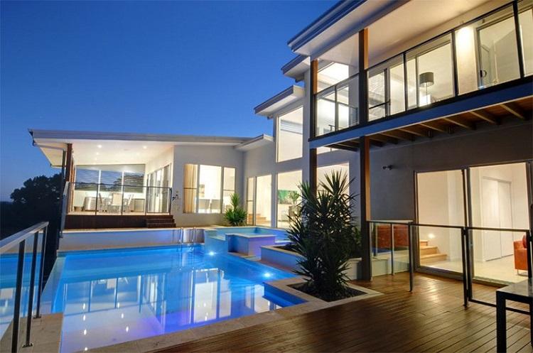 Deck de madeira minimalista instalado em área de piscina exuberante.