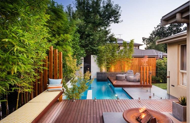 Deck de madeira escura em área da piscina moderna.