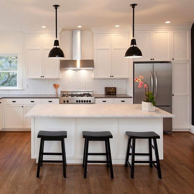 Banquetas baixas de madeira preta em cozinha.