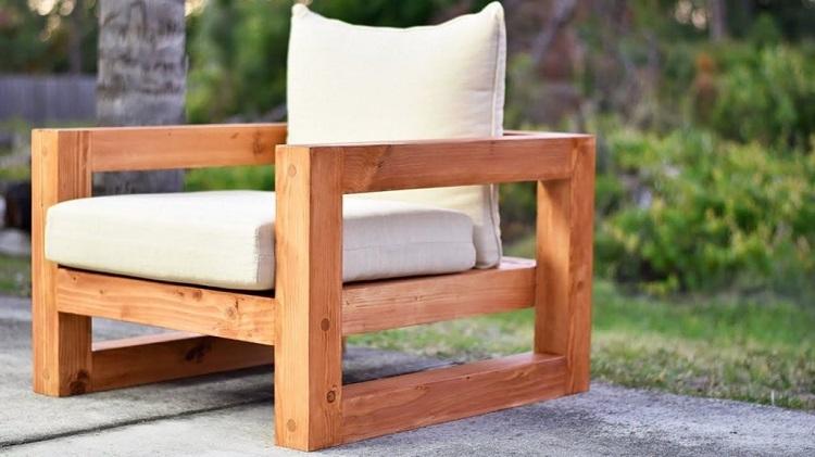 Poltrona de madeira com almofadas soltas.