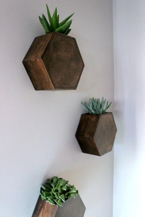 Floreira de madeira escura em formato hexagonal.