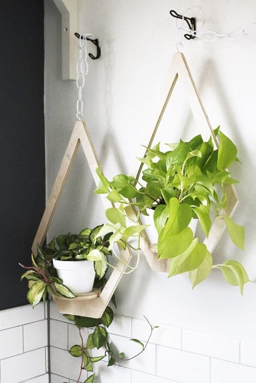 Floreira de madeira pendurada na parede em formato triangular.