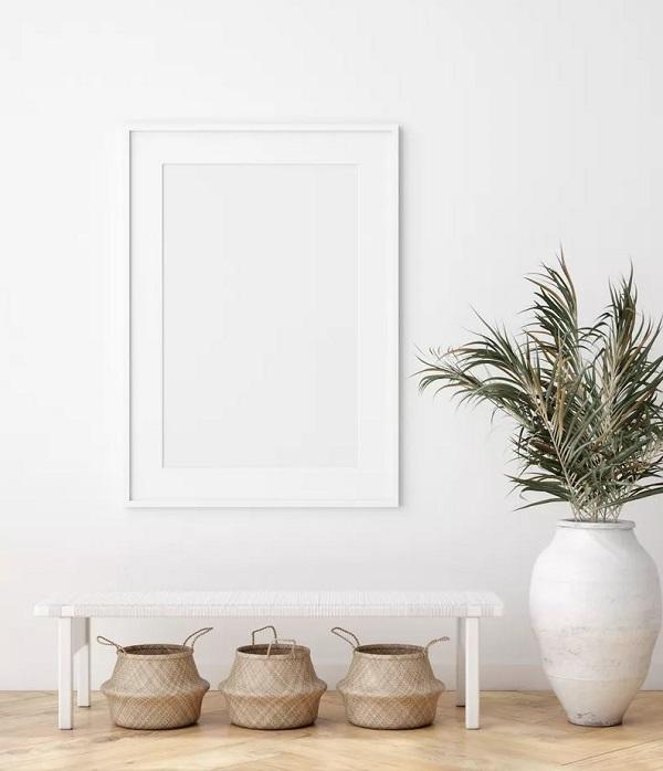 Cômodo com decoração minimalista e objetos naturais, como bando de madeira branca e um vaso de planta.