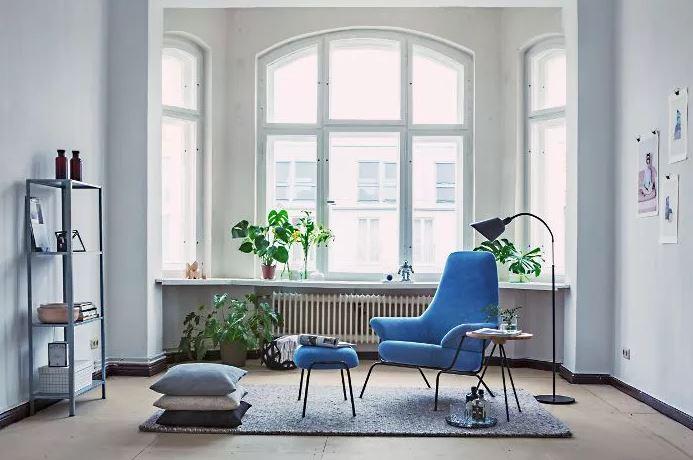Sala minimalista com objetos de texturas diferentes em azul: poltrona, armário, almofada e tapete.