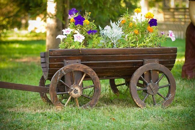 Floreira móvel feita num design de carrinho de madeira.