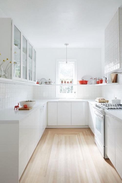 Cozinha com base branca e objetos na cor vermelha.