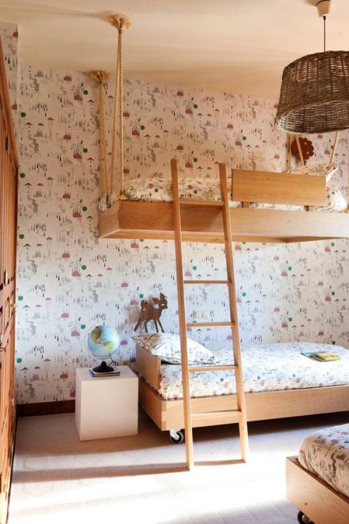 Quarto com beliche de madeira criativo com a cama de cima pendurada por cordas.