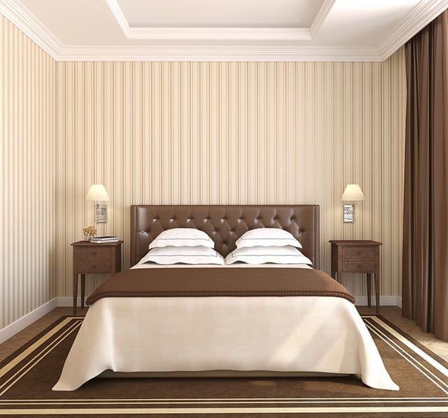 Quarto com cabeceira e tapete marrom e parede e roupa de cama bege.