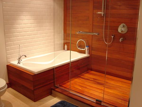 Banheiro com madeira avermelhada de mogno na banheira, assoalho e parede.