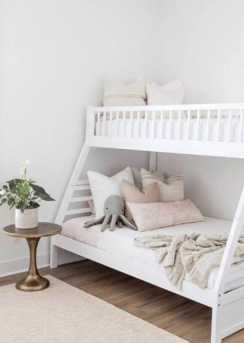 Beliche de madeira branca combinando com detalhes em bege da decoração do quarto.