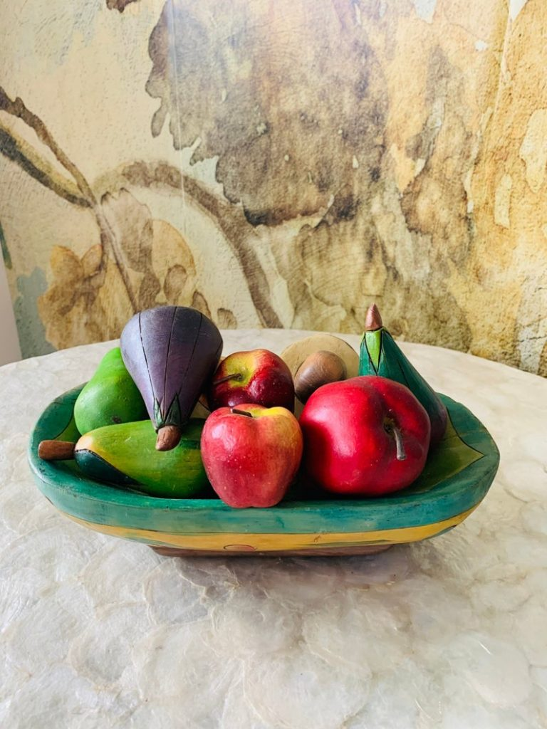 Fruteira de madeira artesanal com frutas decorativas.