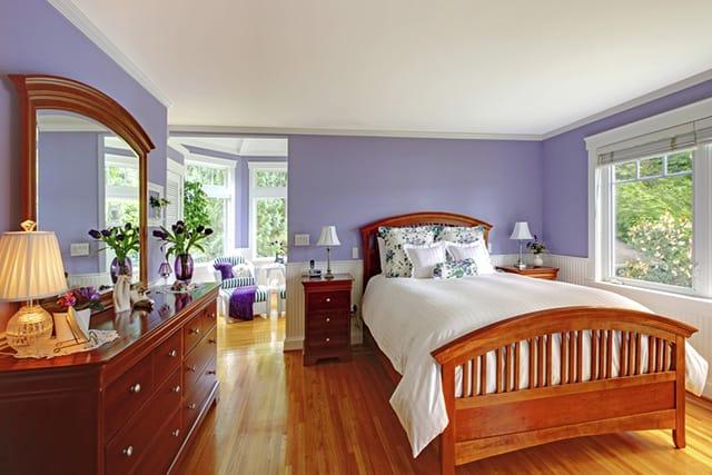 Quarto com móveis de madeira marrom e parede de cor lavanda.