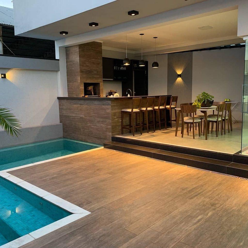 Áre gourmet rústica com piscina e deck de madeira.