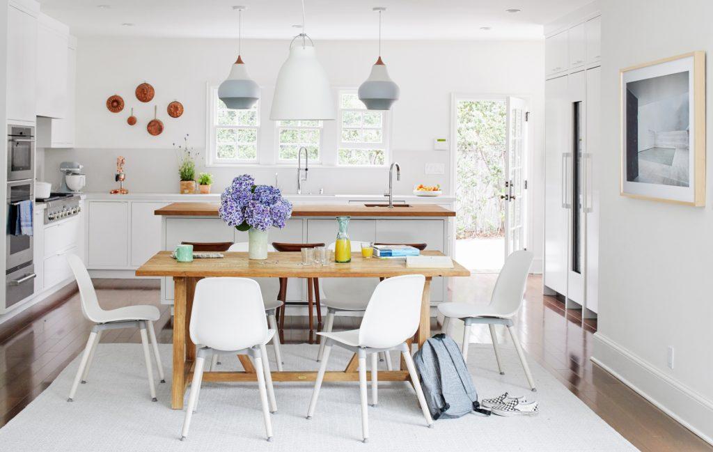 Cozinha aberta nas cores branca e madeira natural.